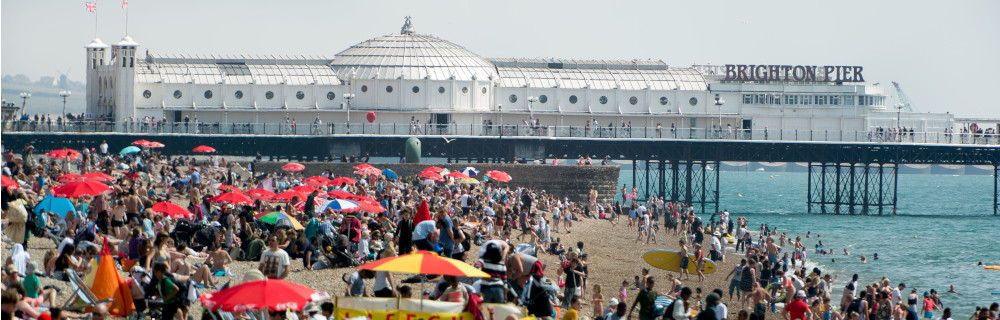 A picture of a very busy Brighton beach with Palace Pier in the background.