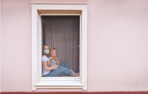A woman and child looking out at the world, during lockdown