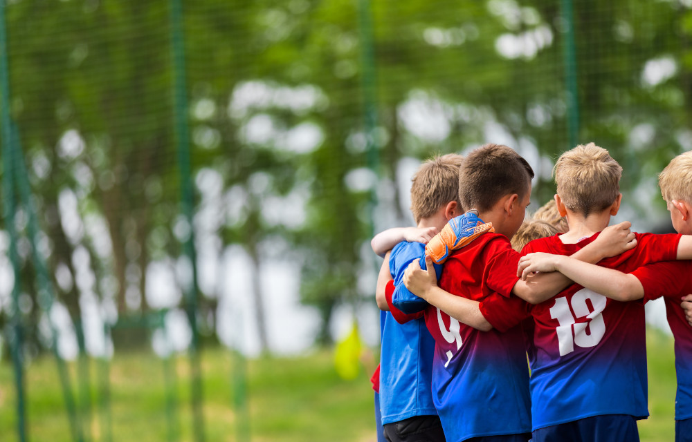 This is a picture of a group of small boys in a football team talk huddle before a match