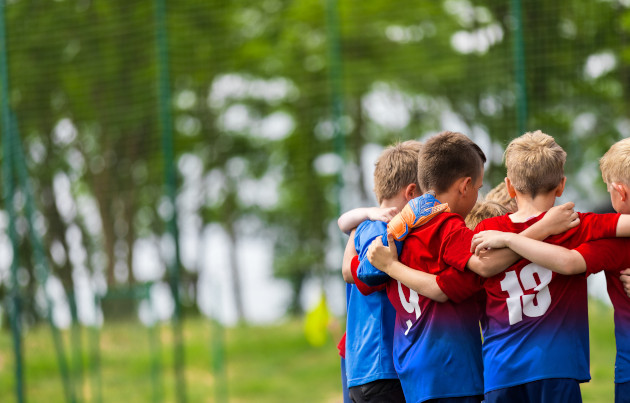 Small footballers in team talk huddle